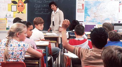 female teacher teaching in front of a chalk board